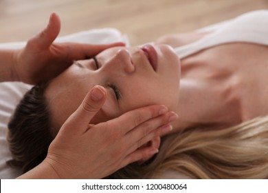Woman enjoying head massage. Acupressure, reiki healing treatment. Relaxation and Alternative medicine concept, holistic care