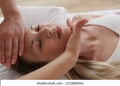 Woman enjoying head massage. Reiki healing treatment. Relaxation and Alternative medicine conept