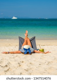 Woman enjoying her holidays on a transat at the tropical beach in Thailand - UNRETOUCHED body.
