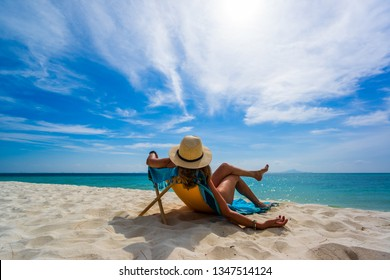 Woman enjoying her holidays on a transat at the tropical beach in Thailand