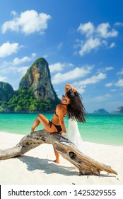 Woman enjoying her holidays at the tropical beach in Thailand - UNRETOUCHED body.