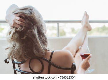 Woman enjoying her red wine on balcony.