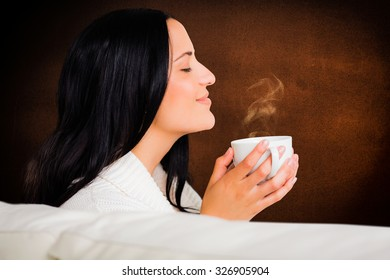 Woman enjoying a lovely drink against orange background with vignette