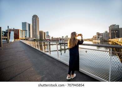 Woman enjoying modern cityscape view standing on the bridge during the morning in Roterdam city