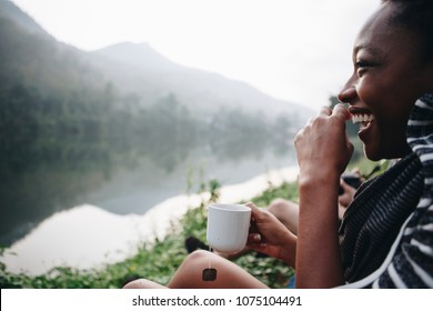 Woman enjoying morning coffee by a river