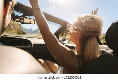 Woman enjoying on a road trip with man driving car. Female sitting in front seat of a convertible car with her hands raised in air, while her boyfriend driving car.