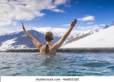 Woman enjoying the panoramic view from the pool in the alps
