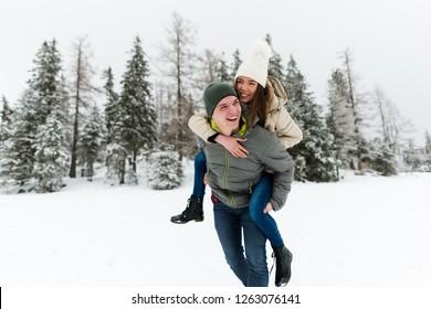 Woman enjoying piggyback ride on her boyfriend's back