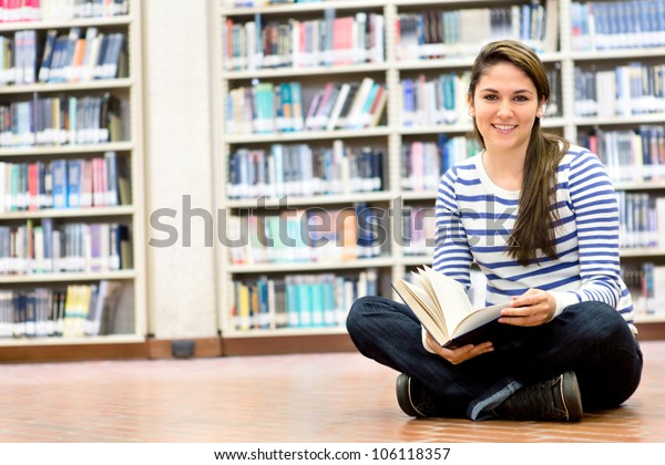 Woman enjoying reading and sitting at the library