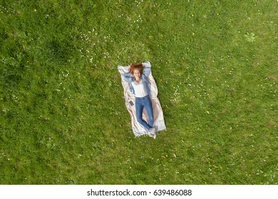 Woman enjoying a relaxing day at the park lying on her back on a rug on fresh green spring grass viewed from high overhead with plenty of copy space