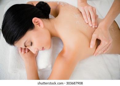 Woman enjoying a salt scrub massage at the health spa