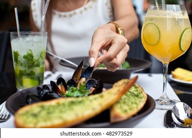 Woman enjoying seafood in a restaurant. Steamed mussels in white wine sauce. Food Concept