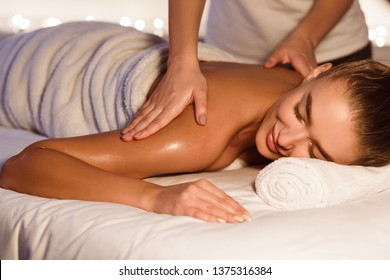 Woman enjoying shoulder massage in the health spa, lying with closed eyes