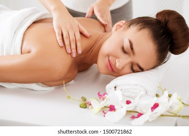 Woman enjoying shoulder massage, relaxing with closed eyes at luxury spa
