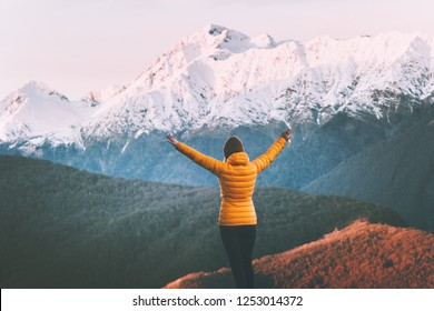 Woman enjoying snowy mountains view adventure lifestyle solo traveling winter vacations outdoor girl raised hands hiking alone harmony with nature