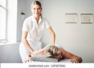 A Woman enjoying spa treatment at salon with masseur worker