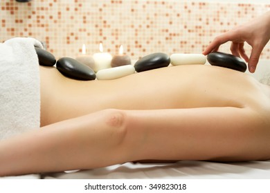 Woman enjoying stone therapy/A female receiving massage and hot rock treatment to back and neck at a beauty salon or day spa facility/Woman Enjoying Stone Therapy/