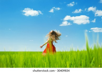 woman enjoying summertime and dancing in the field