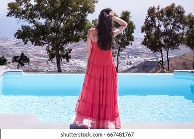 Woman enjoying the sun at infinity summer swimming pool at luxurious resort. Santorini, Greece.