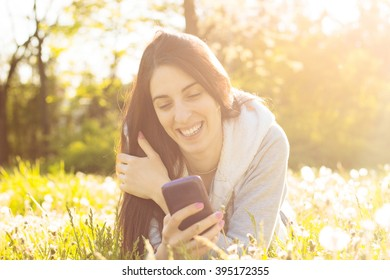 Woman enjoying the sun outdoors in sunset, using her smartphone