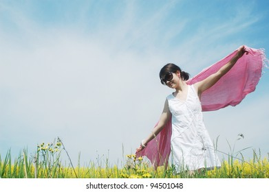 woman enjoying a sunny day on a field of spring flowers.