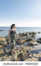 A woman enjoying sunset at a beach.