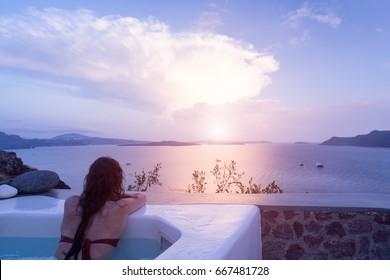 Woman enjoying the sunset at infinity summer swimming pool at luxurious resort. Santorini, Greece.