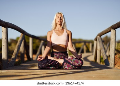 Woman enjoying the sunset on a beautiful beach in Cadiz, Andalusia, Spain. Caucasian female practicing yoga on wooden bridge.