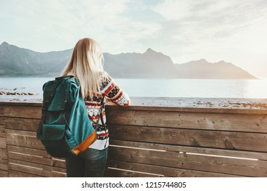 Woman enjoying sunset sea view standing alone on bridge travel lifestyle backpacking vacations outdoor solitude emotions