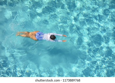 Woman enjoying a swim in a cool refreshing swimming pool.