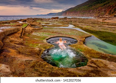 A woman enjoying a swim in the Figure 8 plunge pools.  A set of rock pools located on the rock shelf exposed in low tide only