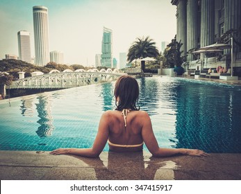 Woman enjoying a swim in a luxurious high rise pool.