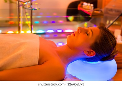Woman enjoying therapy in spa with color therapy, colorful lights stimulating the psyche