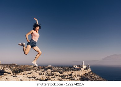 Woman enjoying trip with rv motor home, jumping in the air at camper. Mesa Roldan lighthouse location, Almeria Spain. Happiness and traveling.