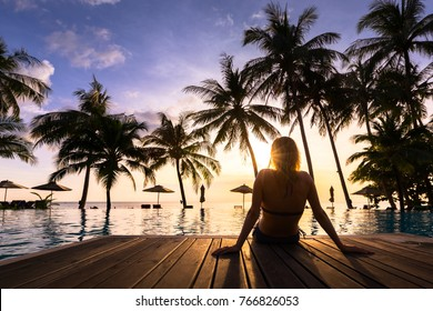 Woman enjoying vacation holidays at luxurious beachfront hotel resort with swimming pool and tropical landscape near the beach