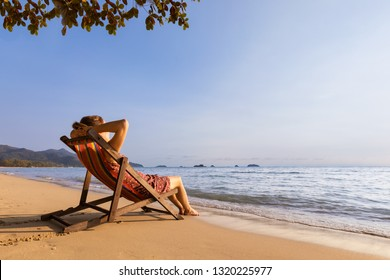 Woman enjoying vacation holidays on the beach and relaxing in a deckchair near the sea, warm sunny summer day for resting and sunbathing