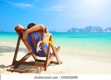 Woman enjoying vacation holidays on the beach and relaxing in a wooden chair near the sea in warm sunny summer day on island Phi Phi, Thailand 