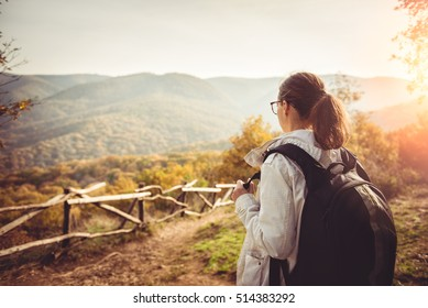 Woman enjoying view on top of mountain during sunset