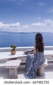 Woman enjoying the view at terrace with sea view. luxurious resort. Santorini, Greece.