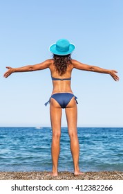 Woman enjoying warm summer day at the seaside.