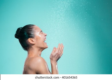 Woman enjoying water in the shower under a shower jet