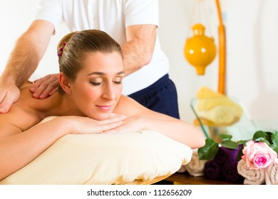 Woman enjoying a wellness back massage in a spa, she is very relaxed (close-up)