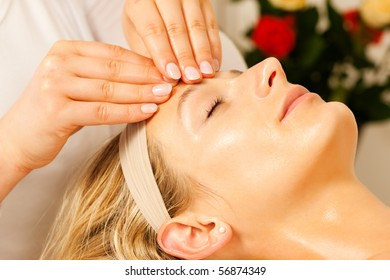 Woman enjoying a wellness head massage in a spa setting with roses in the background, she is very relaxed