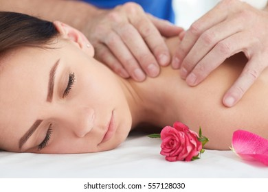 Woman enjoying a wellness neck massage in a spa. Health, beauty, resort and relaxation concept.