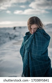Woman enjoying winter in Norway covered with blanket. Lifestyle portrait in scandinavian nature.