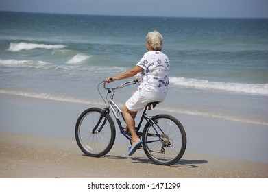 A woman enjoys a bike ride on Ponce Inlet Beach, Florida