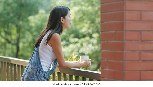Woman enjoys her coffee in the balcony