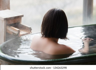 Woman enjoys an outdoor bath at hot springs in Japan