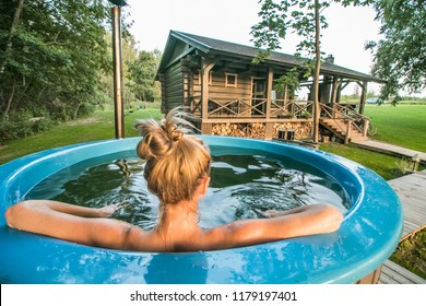 Woman enjoys outdoor hot tub in nature near wooden house