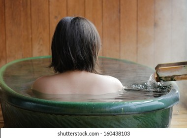 Woman enjoys an outdoor steamy bath at hot springs in Japan